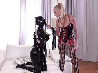 Mistress plays dominant with slave girl dressed in latex costume